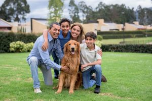 Happy Latin American family with a dog at home playing in the backyard and looking at the camera smiling