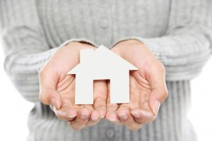 hands-of-a-woman-holding-a-white-paper-house