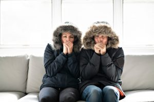 couple-sitting-on-couch-with-parkas-on