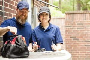 two-technicians-standing-over-outside-ac-unit-with-tool-bag